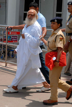 Police escort spiritual leader Asaram Bapu (L) outside an airport after his arrest in Jodhpur, in India's desert state of Rajasthan September 1, 2013. Police arrested Bapu from India's central Madhya Pradesh state late on Saturday night and transited him to neighbouring Rajasthan for further questioning on charges of sexual assault on a minor.